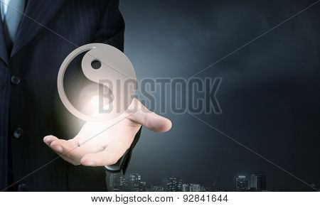 Close up of businessman holding yin yang symbols in palm