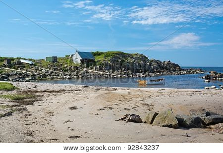 Small wood boat in rocky coastal landscape and fisherman's house