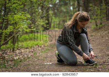 Female Jogger Tying Sporty Shoes