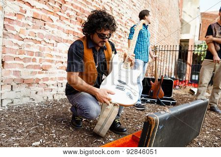 A street musiciam unpacking his guitar