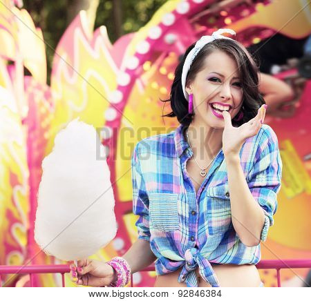 Toothy Smile. Young Woman With Cotton Candy In Amusement Park