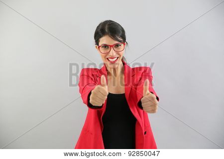 Beautiful brunette girl in red, showing thumbs up
