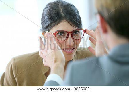Optician testing new eyeglasses on woman