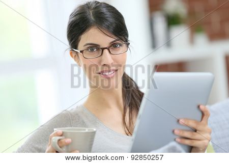 Brunette girl relaxing in sofa connected on tablet and drinking hot tea