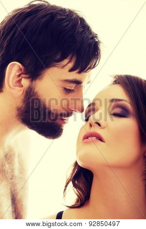 Handsome shirtless man fondly whispering to woman's ear.
