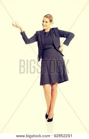 Happy businesswoman presenting copy space.