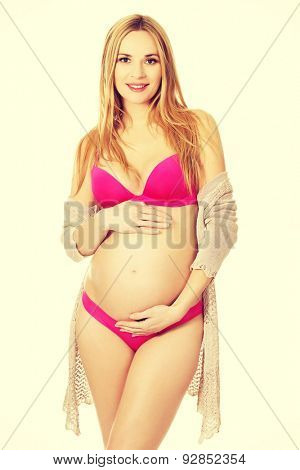 Well groomed pregnant woman in lingerie and cardigan