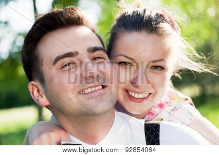 Young smiling couple in love portrait in summer park. Looking at the camera. Date, fiance with fiancee concepts