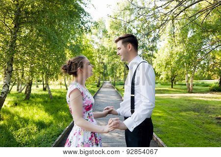 Young couple in love holding hands and looking each other in the eyes in summer park , straight wooden path. Woman in dress and man wearing shirt with suspenders.