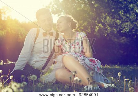 Romantic couple in love flirting on grass in sunny spring park. Dating, vintage romance, sun flare.