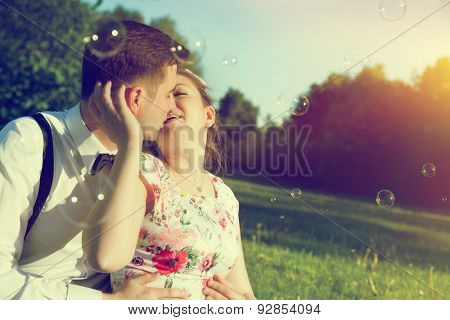 Young romantic couple kissing with love in sunny summer park. Dating, fiance with fiancee, elegant romance. Vintage, soap bubbles