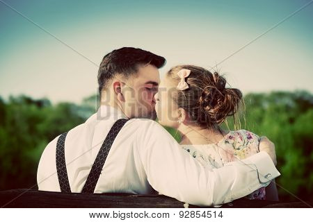 Young couple in love kissing on a bench in summer park. Man wearing shirt with suspenders. Happy future, marriage concepts. Vintage