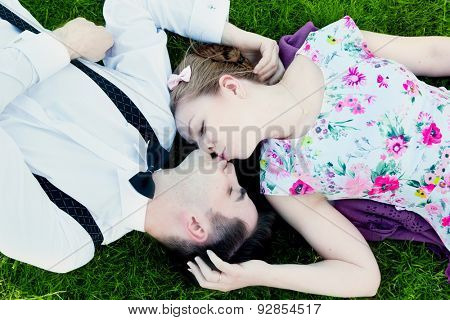 Happy couple in love kissing while lying on summer grass. View from above