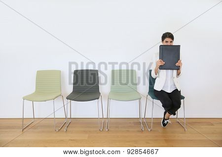 Woman in waiting room for job interview being anxious