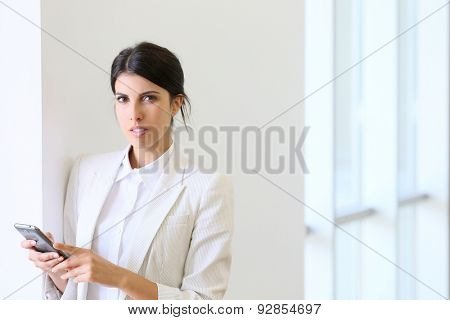 executive woman using smartphone in hallway