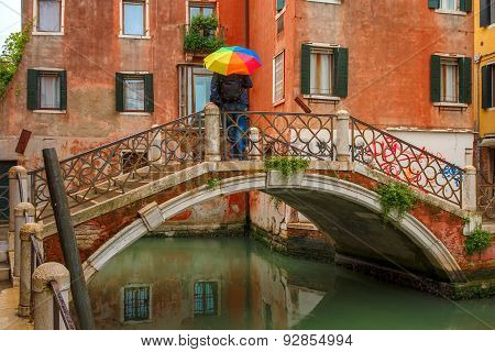 Man with umbrella on bridge over Venetian canal