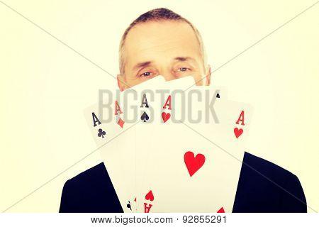 Portrait of elegant man with four aces.