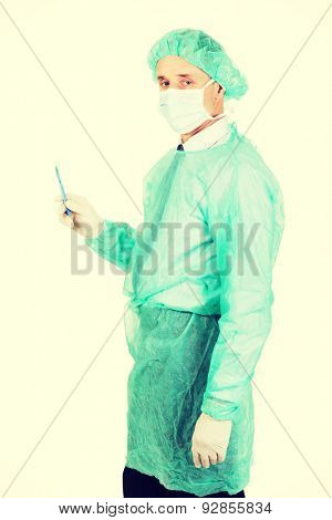 Mature doctor with a scalpel wearing protective clothes.