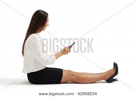 sideview photo of woman in formal wear sitting on the floor and using her smartphone. isolated on white background