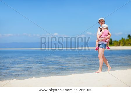 Mother With Baby Walking Along Tropical Coast
