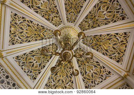 Ceiling And Chandelier Detail In a Gold Room