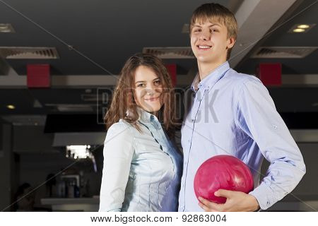 Young couple in bowling club having fun together