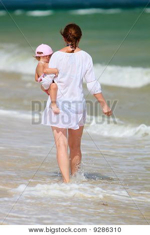 Mother And Baby Walking Along Beach