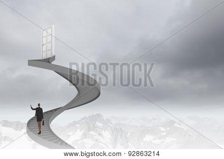 Businesswoman walking up staircase to door in sky