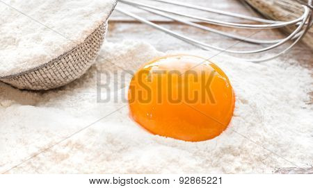 Egg yolk in flour on a wooden board