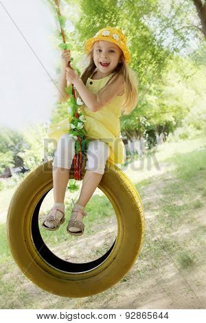 Girl In Yellow Dress On Tire Swing