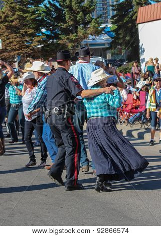 Policeman And Lady Dancing On The Street During Calgary Stampede Parade
