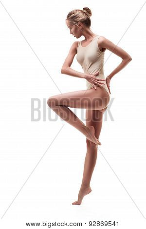 young beautiful dancer in beige swimsuit