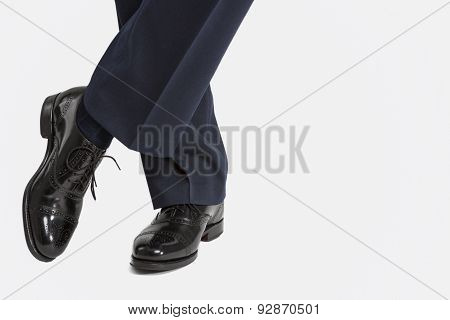 Closeup Of Male's Stylish Oxfrod Brogue Shoes Posing With Legs Crossed.