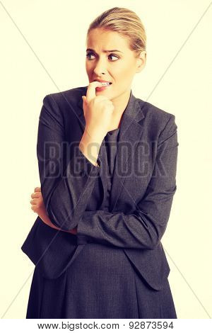 Stressed businesswoman biting her nails.