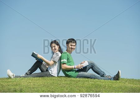 Young Asian Couple Sitting Side By Side And Reading Their Books