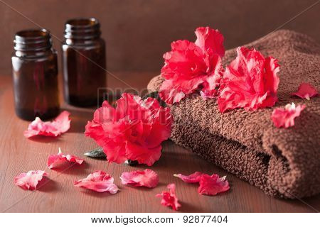 spa bathroom with azalea flowers essential oil on dark rustic background