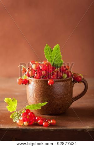 fresh redcurrant in cup over rustic wooden background