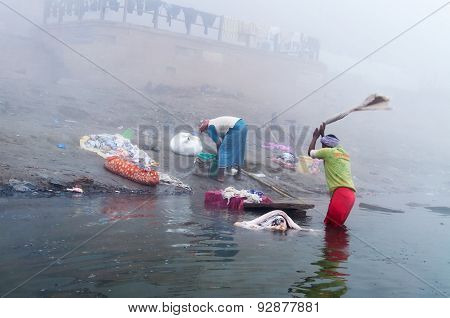 Indian Man Washes Clothes In The Holy Water Of The River Ganges At Cold Foggy Winter Morning. Varana