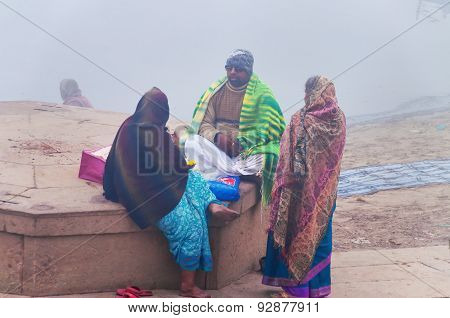 Group Of Indian People On The Ghat Near Sacred River Ganges At Cold Foggy Winter Morning
