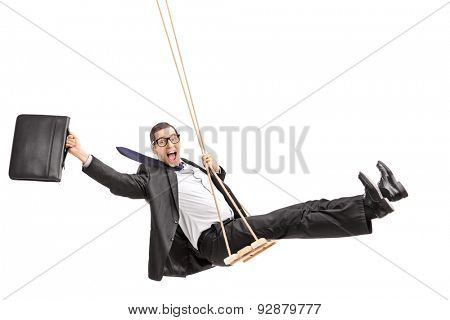 Studio shot of a delighted young businessman swinging on a swing and holding a suitcase isolated on white background