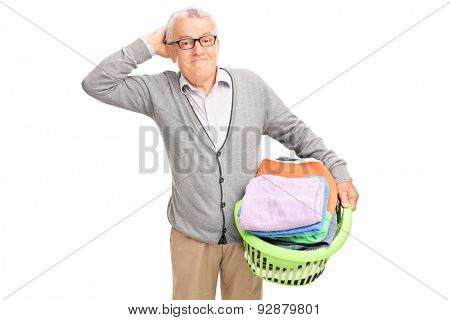 Confused senior holding a laundry basket full of clothes and looking at the camera isolated on white background