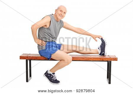 Senior in sportswear sitting on a wooden bench and stretching his leg isolated on white background
