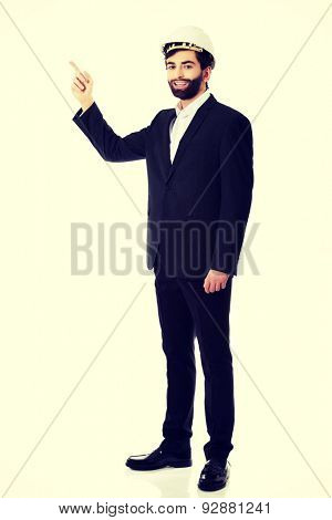 Smiling handsome businessman with hard hat pointing up.