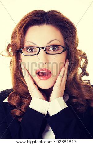 Shocked businesswoman holding her head in amazement.