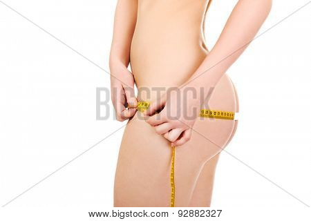 Slim undressed woman measuring her hips.