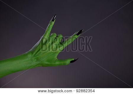 Green monster hand showing heavy metal gesture, studio shot on black background