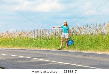 "Beautiful young woman hitch hiking- in auto-stop ""votes"" on road with luggage"