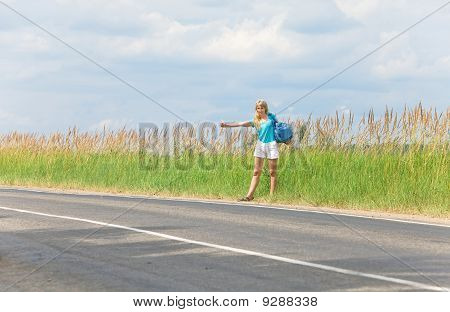"Beautiful young woman hitch hiking- in auto-stop ""votes"" on road"