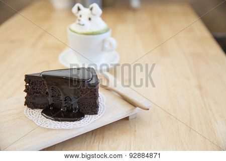 Chocolate Cake And  Green Tea Topping Made By Milk Foam Top On The Cup Of Hot Green Tea