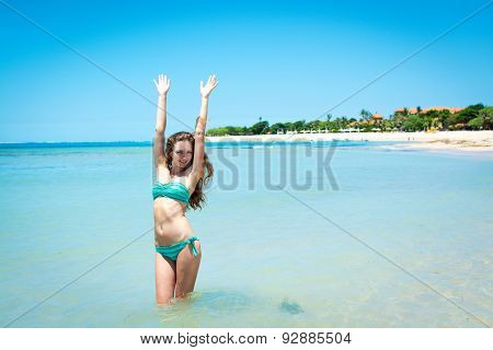 Young woman smiling at camera in front of sea shore